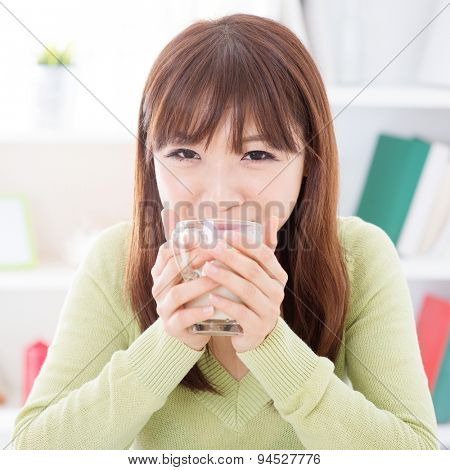 Portrait of happy Asian girl drinking soymilk as breakfast. Young woman indoors living lifestyle at home.