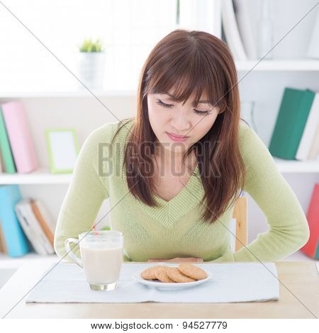 Woman holding stomach and suffering stomachache, while having dairy milk and cookies as breakfast, sitting at dining table.Young people indoors living lifestyle at home.
