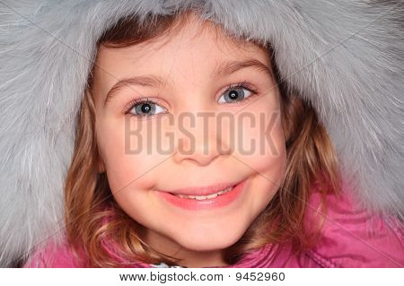 Portrait Of Little Girl In Big Fur Hood, Looking At Camera And Smiling