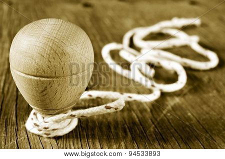 a traditional wooden spinning top with a string coiled in its axis on a rustic wooden surface, in sepia toning