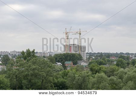 Three high tower crane building a new house flats in a beautiful green park area of the city