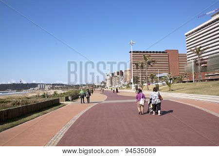 Pedestrians Walking Along Paved Promenade On Beach Front