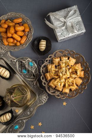 Islamic festive still life. Eid is celebrated with special sweets and distributing gifts. Studio shot from the top.
