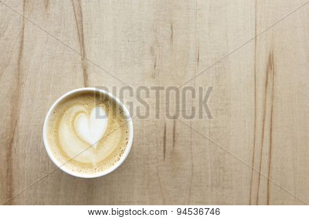 Cappuccino With Heart In Paper Take Away Cup On Light Wood Table. From Above.