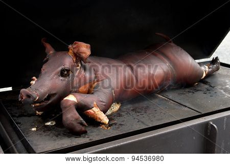 Whole Smoked Suckling Piglet On Hot Griddle.