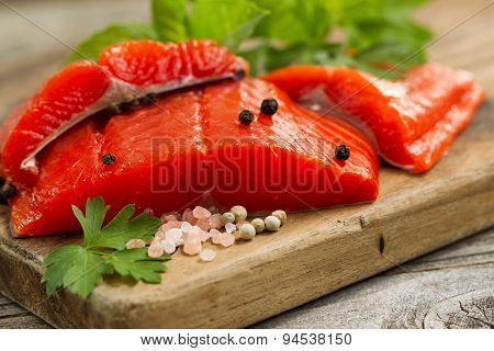 Fresh Copper River Salmon Fillets On Rustic Wooden Server With Spices And Herbs