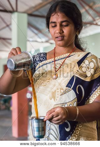 Young Woman Cools Coffee By Pouring In The Air.