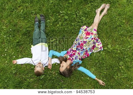 Cute girl with her little brother lying on the green grass, top view.