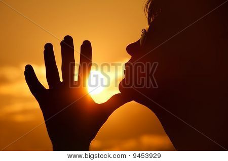 Silhouette of person in profile against background of orange sunset sky