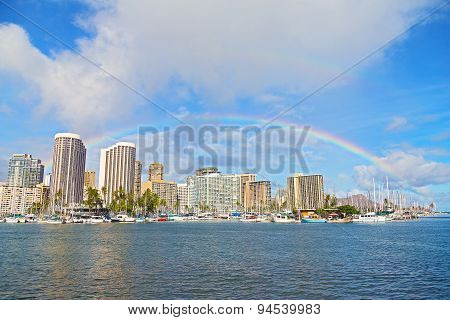 Rainbow over Waikiki beach resort and marina in Honolulu Hawaii USA.