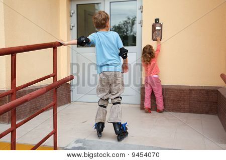 Boy on roller skates and little girl in front of house.