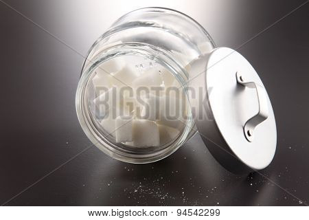 White lump sugar in a glass jar on a gray background, sweet sugar in ware with a glass opened, nobody.