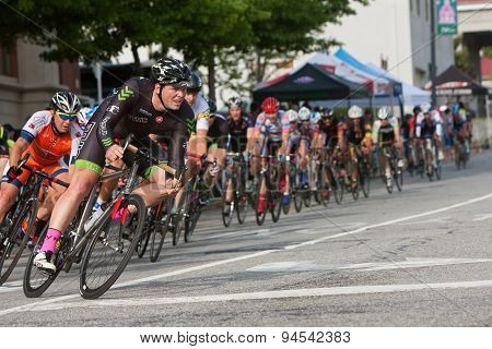 Male Cyclist Leads Pack Into Turn In Amateur Bike Race