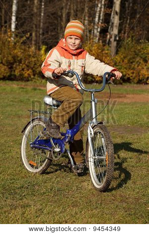 Boy on bicycle in autumn park on sunny day.