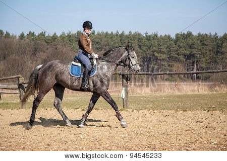 Young woman riding a horse.