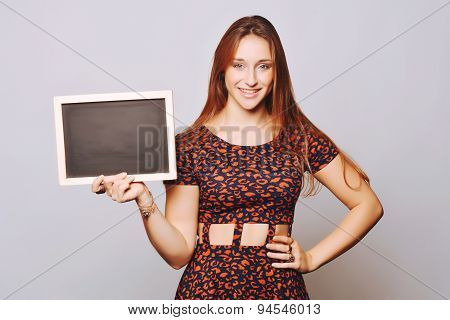 Young Girl Holding A Chalkboard.