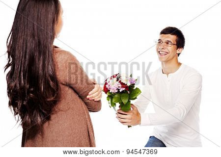 Young smiling man in glasses down on one knee giving bouquet of flowers to young woman on white isolated background