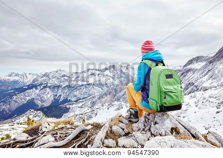 Female hiker with backpack sitting on rock of mountain top enjoying view of valley below