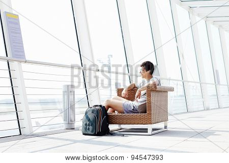 Young smiling man in glasses and headphones sitting on chair in airport departure lounge