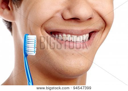 Dental hygiene concept with close up of male smile with healthy teeth and blue toothbrush