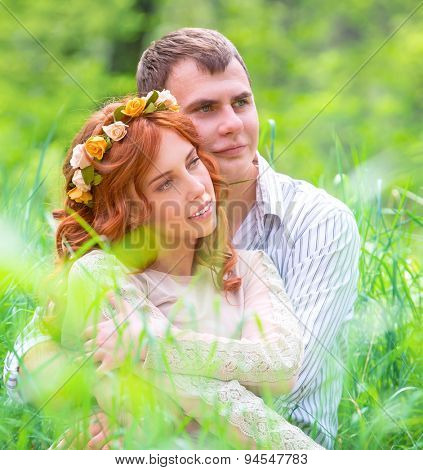 Portrait of beautiful gentle loving couple sitting on the grass in forest, wedding day, enjoying romantic relationship
