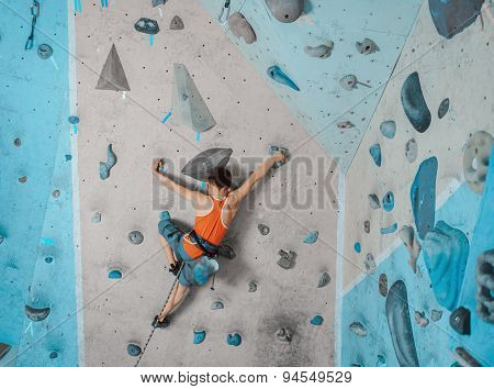 Boy In Safety Equipment Climbing In Gym