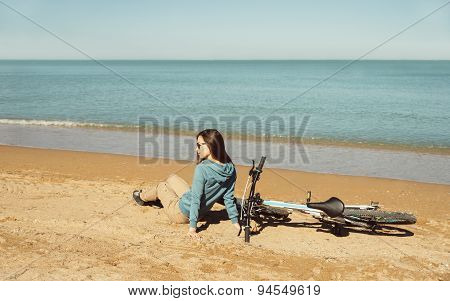 Woman With A Bicycle Sitting On Beach
