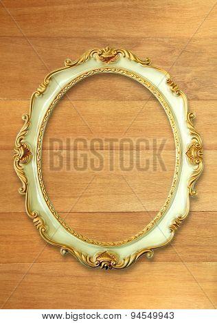 Vintage golden frame on wooden wall
