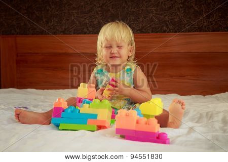 Little Blonde Girl Plays Toy Constructor Sitting On Sofa
