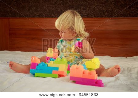 Little Blonde Girl Plays Toy Constructor