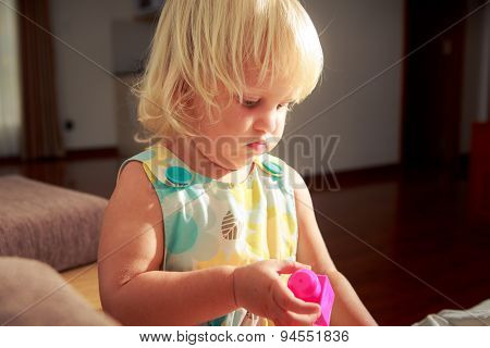 Blonde Girl Plays Toy Constructor