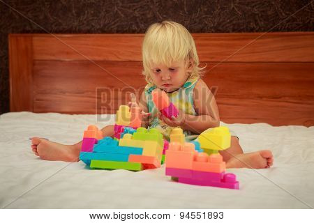 Little Girl In Pink Looks With Interest At Toy Constructor