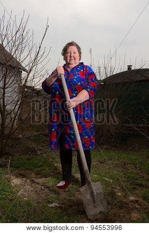 An Elderly Woman With A Shovel, Cultivated Garden.
