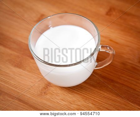 Mug of the cow milk on a wooden surface