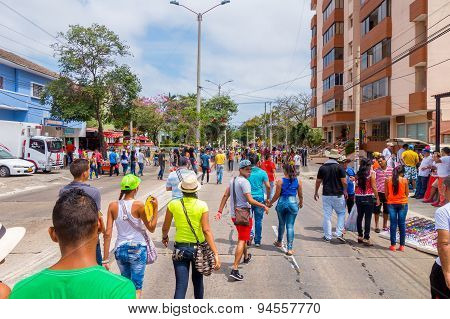 Multiple spectators street waking away from the Carnival parade colorful vendors in Colombia's most