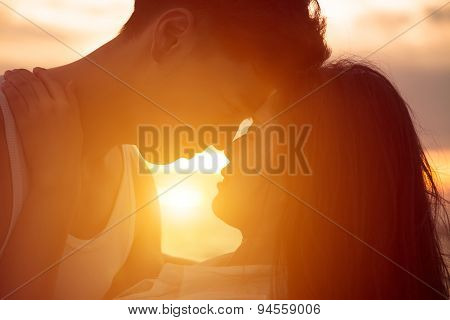 young happy couple kissing at sunset on beach