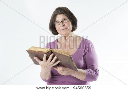 Elderly Woman With An Old Book In Her Hands.