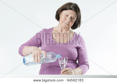 Elderly Woman Pours Water Into A Glass.