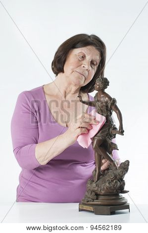 Elderly Woman Wipes The Dust From The Interior Sculptures.