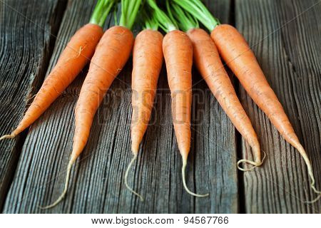 Carrots bunch of fresh organic vegetarian food on rustic wooden background