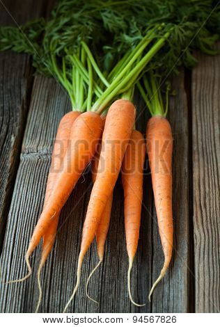 Bunch of carrots healthy vegetarian raw snack on vintage wooden background