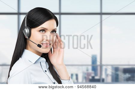 Portrait Of Smiling Cheerful Support Phone Operator In Headset. New York Panoramic Office Background