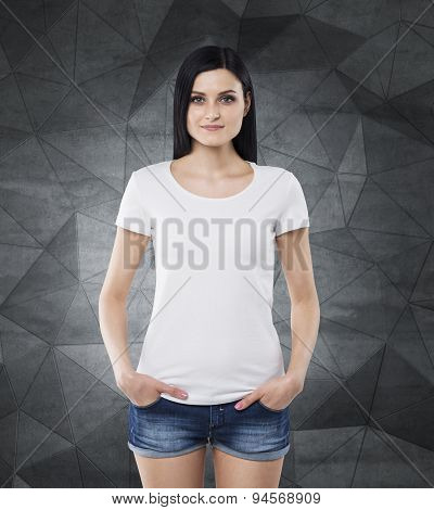 Brunette Girl In A White T-shirt And Denim Shorts. Contemporary Dark Grey Background.