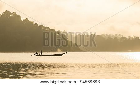 Silhouetted Fisherman And Boat With Mountain Background