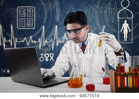 Scientist With Laptop And Chemical Glassware