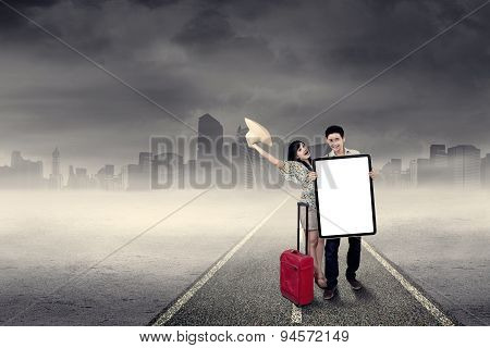 Two Tourists Holding Billboard Outdoors