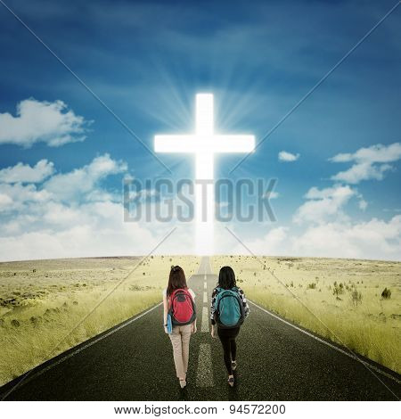 Two Students Walking Toward A Cross