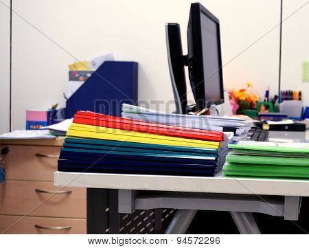 Stack Of Colorful Folders And Multiple Documents In The Training Office
