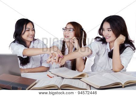 Three Schoolgirls Pile Up Their Hands