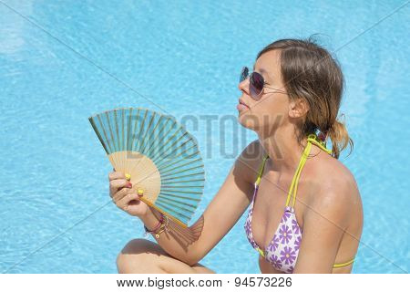 Girl Cooling With The Fan By The Pool